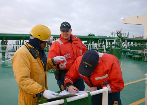 one man wearing yellow jacket, hat and gloves and two other men wearing orange jacket standing on deck while one is writing on paper