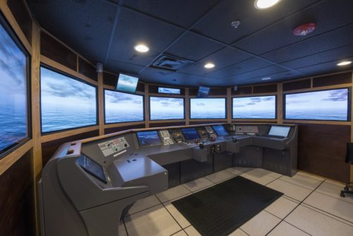 ship control room simulator with screens and panel of buttons and controls