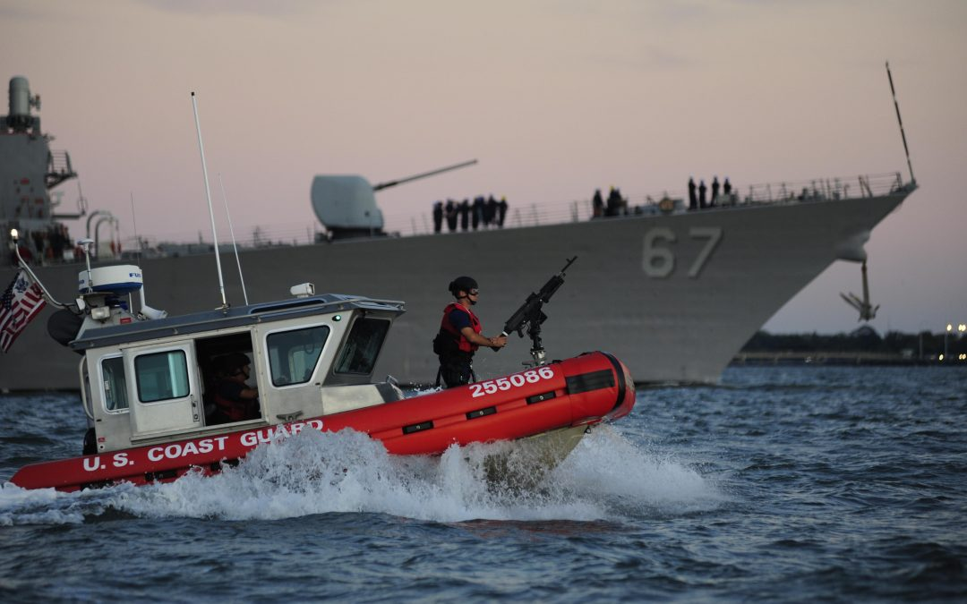 Guard wearing protective gear on moving red US Coast Guard boat with large Navy ship behind